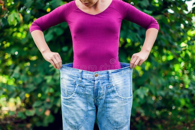 Junge Frau, die in der Hand große lose Jeans mit Gewicht des Apfels - trägt stockfotos