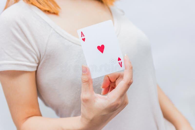Junge Frau, die in der Hand Pokerkarte mit Kombination von voll hält stockbild