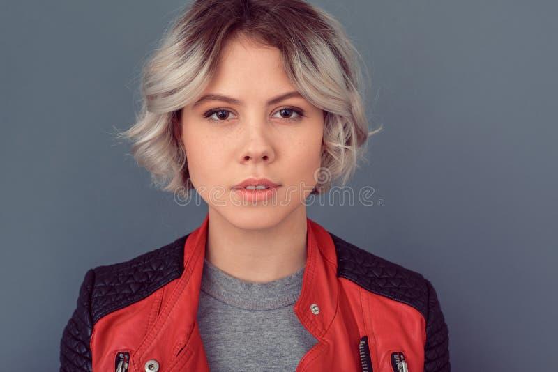 Junge Frau, die in der Lederjacke auf grauer Wandsinnlichkeitsnahaufnahme steht stockfotografie