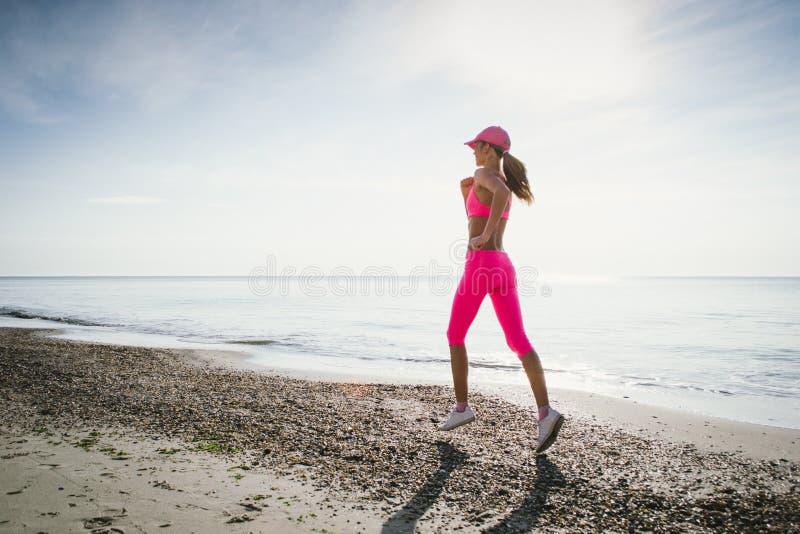 Junge Frau, die an der Seeküste bei Sonnenaufgang oder Sonnenuntergang läuft stockbild