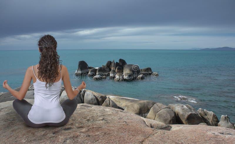 Junge Frau, die an der Seeküste meditiert stockfotos