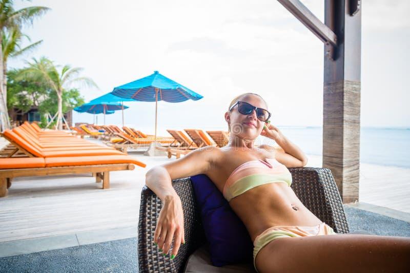 Junge Frau, die an der Strandbar sich entspannt lizenzfreie stockfotografie