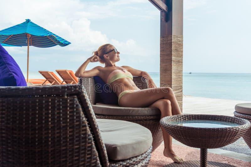 Junge Frau, die an der Strandbar sich entspannt stockfotos