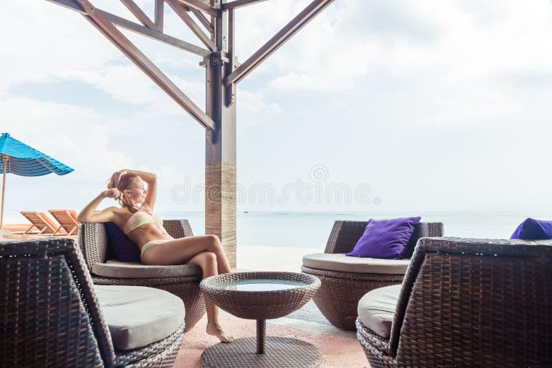 Junge Frau, die an der Strandbar sich entspannt lizenzfreies stockbild