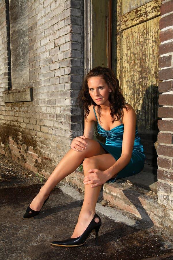 Junge Frau, die in der Tür sitzt stockfotografie