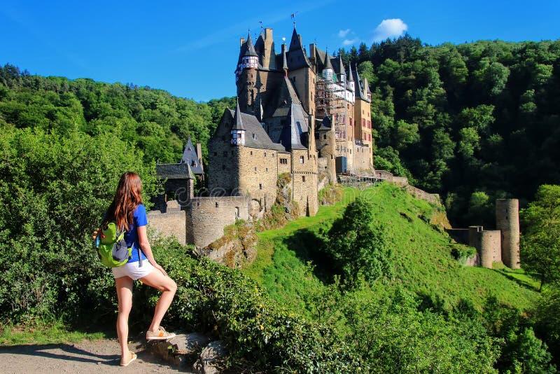 Junge Frau, die an der Unterlassung von Eltz-Schloss in Rheinland steht lizenzfreies stockbild