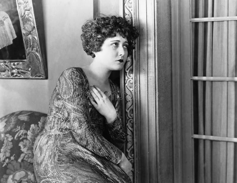 Junge Frau, die an der Wand, schauend sich lehnt traurig (alle dargestellten Personen sind nicht längeres lebendes und kein Zusta stockfotografie
