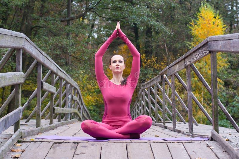 Junge Frau, die in der Yogalage auf Holzbrücke im Herbst steht stockfoto
