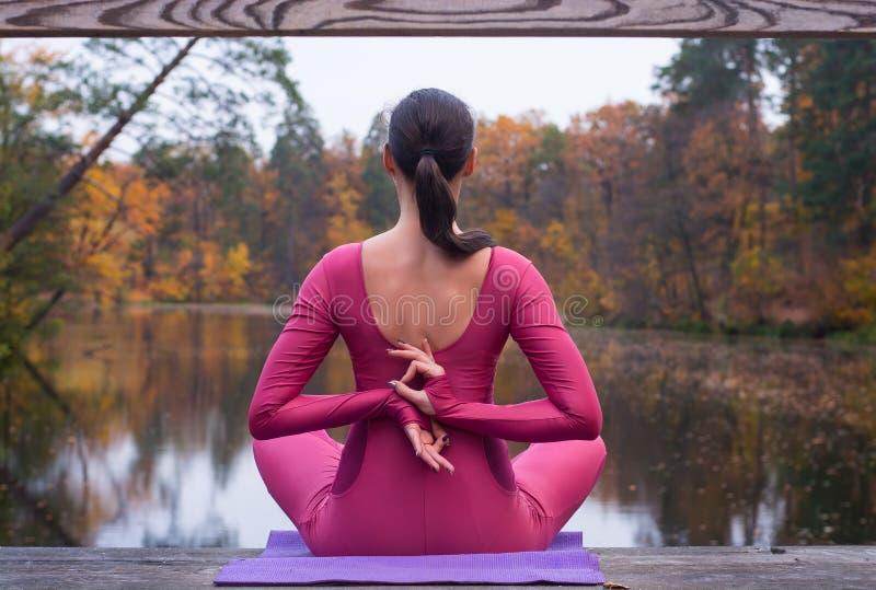 Junge Frau, die in der Yogalage auf Holzbrücke im Herbst steht lizenzfreie stockfotografie