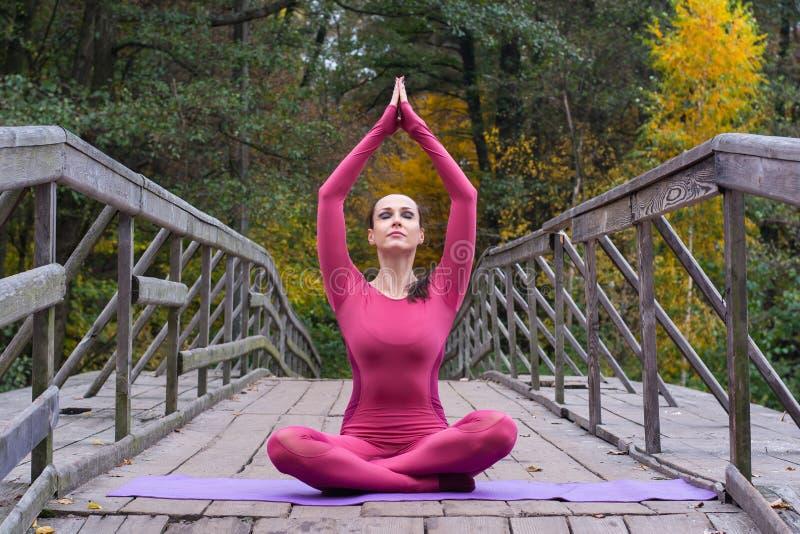 Junge Frau, die in der Yogalage auf Holzbrücke im Park steht stockfotos
