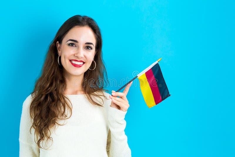 Junge Frau, die deutsche Markierungsfahne anhält stockbild
