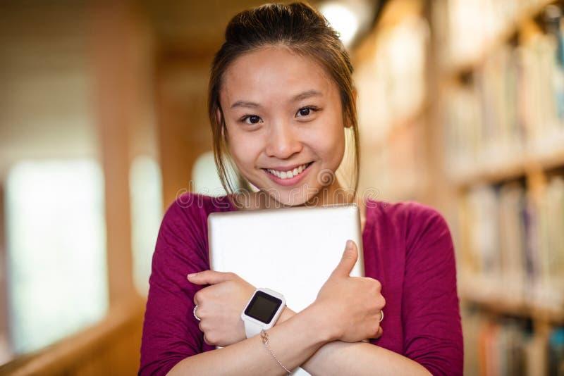 Junge Frau, die digitale Tablette in der Bibliothek hält stockfotos