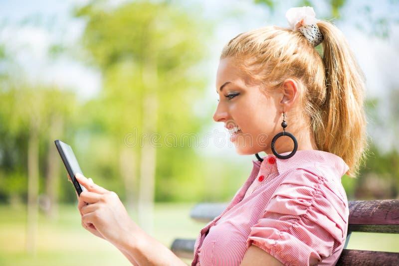 Junge Frau, die digitale Tablette im Park verwendet lizenzfreie stockbilder