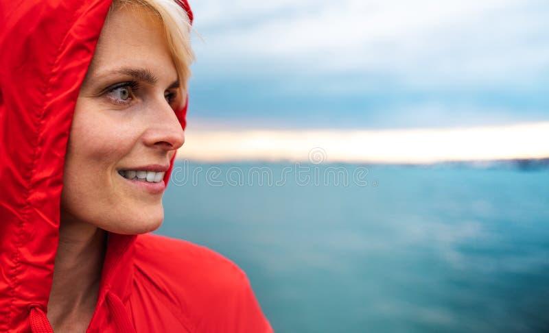 Junge Frau, die draußen auf Strand an der Dämmerung steht Kopieren Sie Platz lizenzfreies stockbild