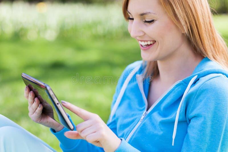 Junge Frau, die draußen digitale Tablette verwendet stockfotografie