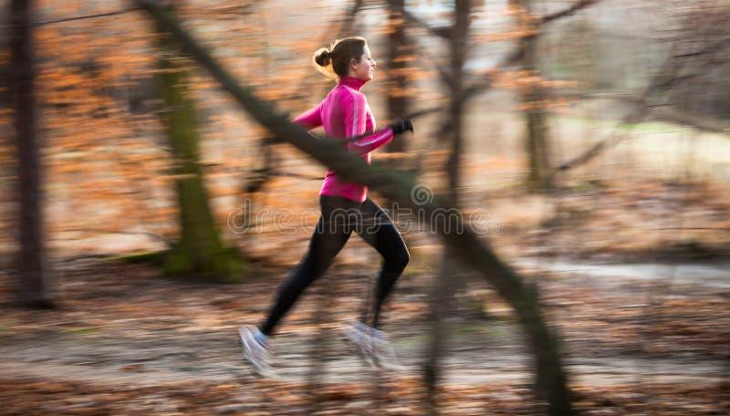 Junge Frau, die draußen in einen Stadtpark läuft lizenzfreie stockfotografie