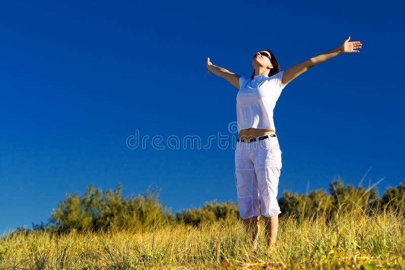Junge Frau, die draußen genießt stockfotografie