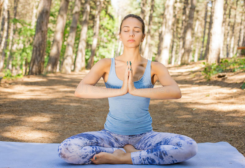 Junge Frau, die draußen im Frühjahr Sommerpark meditiert stockfotos