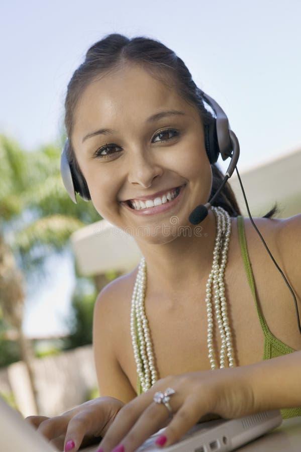 Junge Frau, die draußen Laptop und Kopfhörer verwendet lizenzfreies stockbild