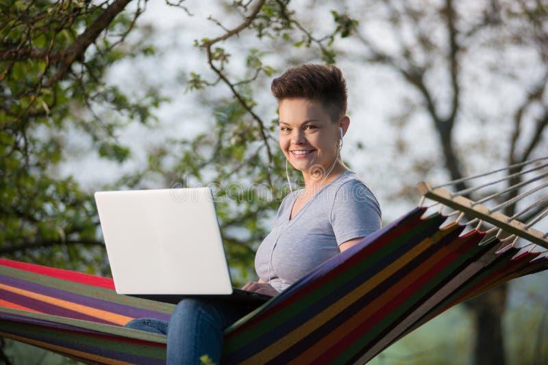 Junge Frau, die draußen Laptop verwendet lizenzfreie stockfotos