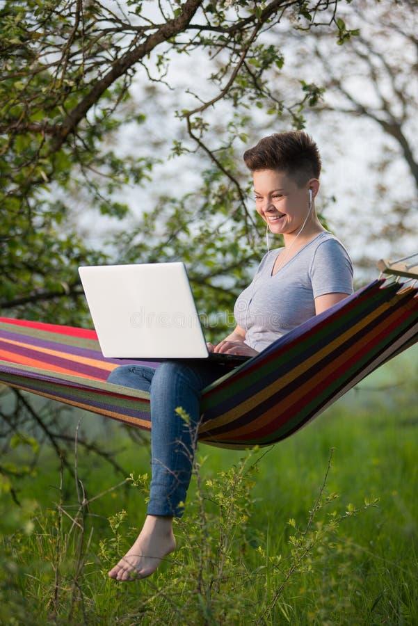 Junge Frau, die draußen Laptop verwendet stockfoto