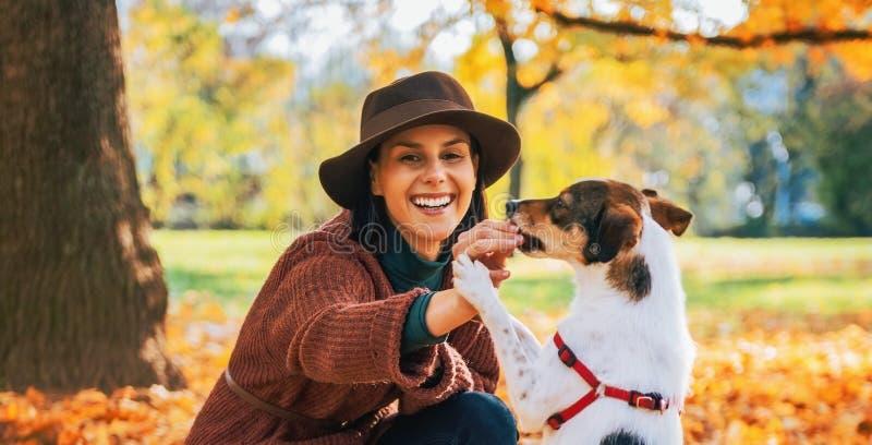 Junge Frau, die draußen mit Hund im Herbst spielt stockbild