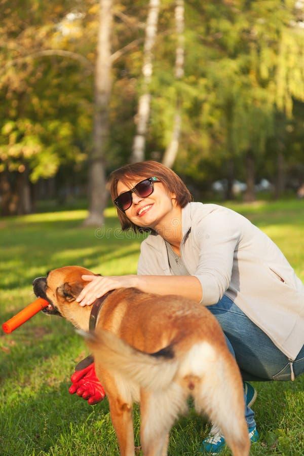Junge Frau, die draußen mit Hund im Park spielt lizenzfreie stockbilder