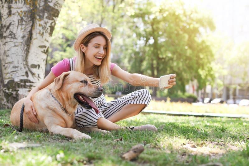 Junge Frau, die draußen selfie mit ihrem Hund nimmt stockfoto