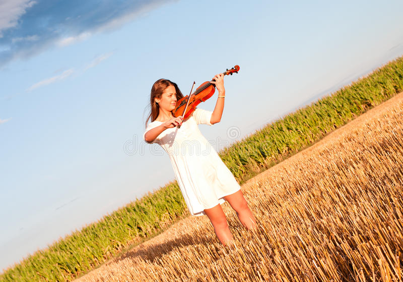 Junge Frau, die draußen Violine spielt stockfotografie