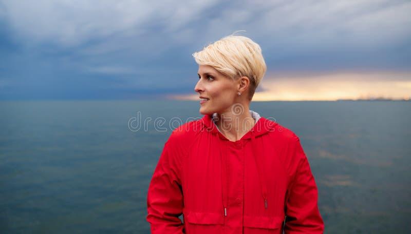 Junge Frau, die drau?en auf Strand an der D?mmerung steht Kopieren Sie Platz lizenzfreie stockfotografie