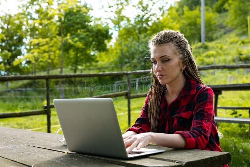 Junge Frau, die drau?en an ihrem Laptop arbeitet stockbild