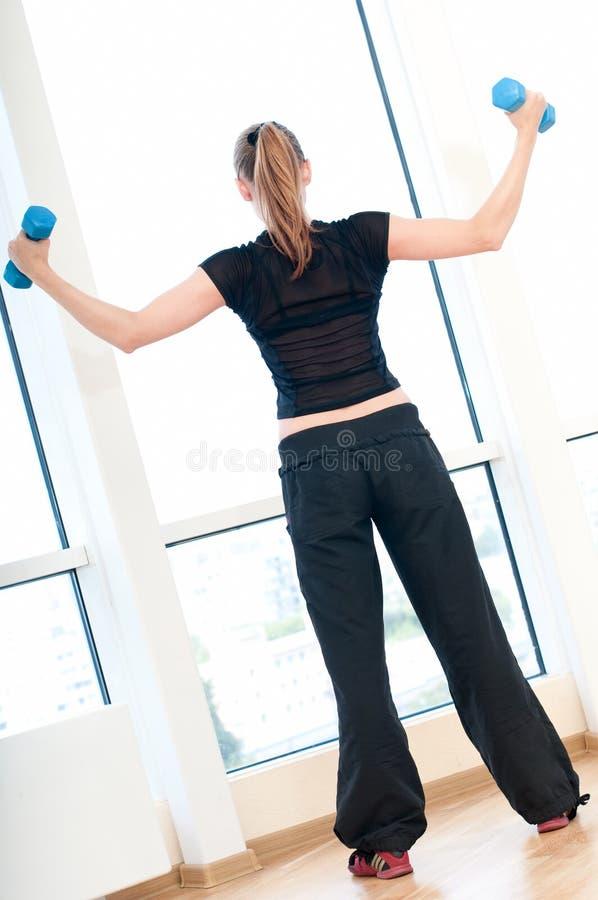 Junge Frau, die Dumbbellübungen tut stockfoto