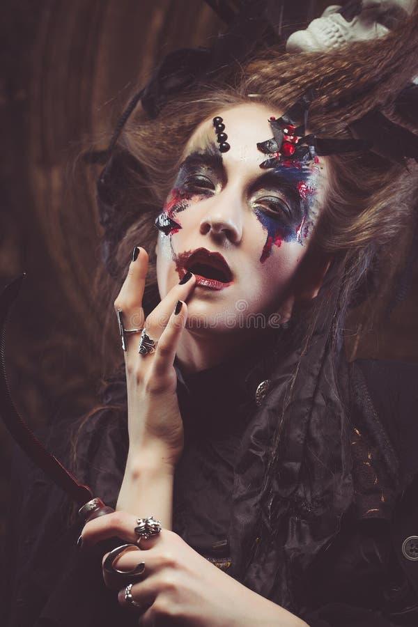 Junge Frau, die dunkles Kostüm trägt Hell bilden Sie und rauchen Sie Halloween-Thema lizenzfreies stockbild