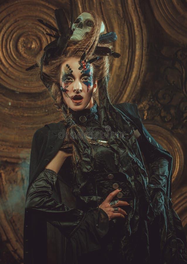 Junge Frau, die dunkles Kostüm trägt Hell bilden Sie und rauchen Sie Halloween-Thema lizenzfreie stockfotografie