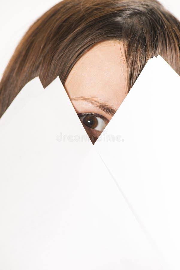 Junge Frau, die durch Blätter Papier schaut stockfoto