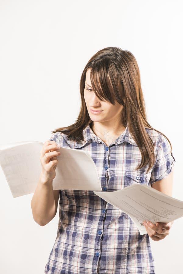Junge Frau, die durch Blätter Papier schaut lizenzfreies stockbild