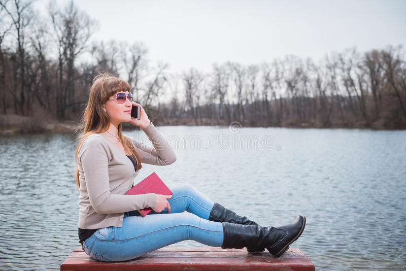 Junge Frau, die durch das Telefon, mit Buch auf ihren Händen, täglicher Lebensstil, Fluss auf dem Hintergrund, Frühling, sonniger lizenzfreies stockbild
