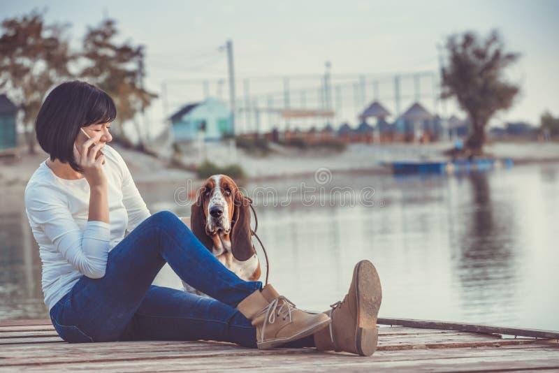 Junge Frau, die durch den Fluss mit ihrem Hund sitzt und am Telefon spricht stockbild