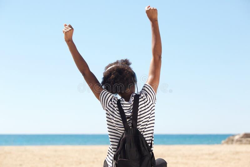 Junge Frau, die durch den Strand sitzt und Musik auf Kopfhörern vorschreibt stockfotografie
