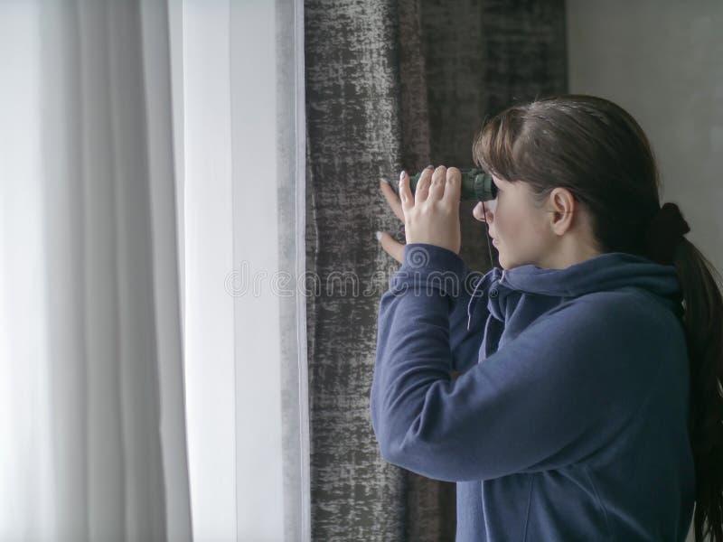 Junge Frau, die durch Ferngläser durch das Fenster aufpasst stockbild