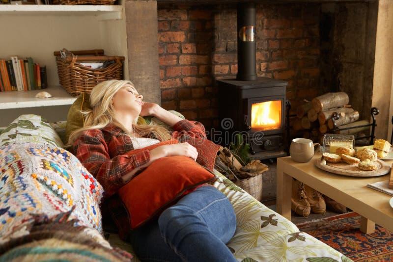 Junge Frau, die durch Feuer sich entspannt stockfotos