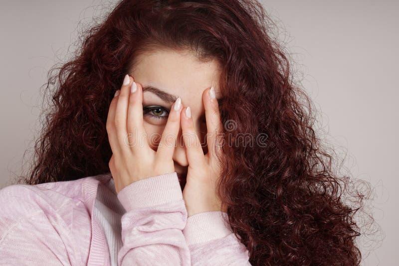 Junge Frau, die durch Finger späht lizenzfreies stockbild