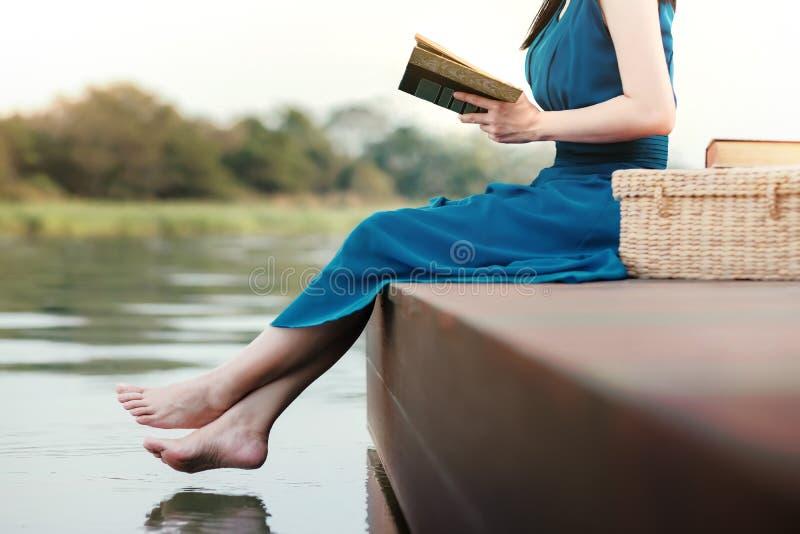 Junge Frau, die durch Flussufer sich entspannt Sitzen auf Plattform und Ablesen-Buch lizenzfreie stockfotos