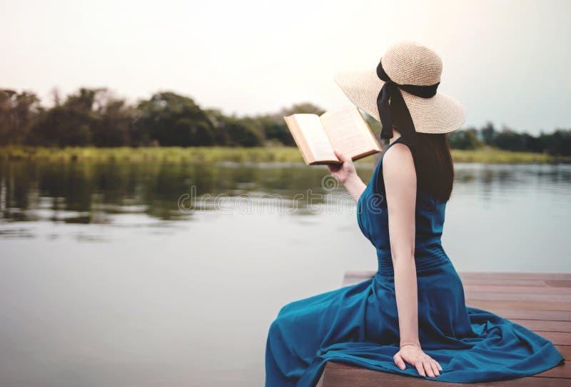 Junge Frau, die durch Flussufer sich entspannt Sitzen auf Plattform und Ablesen-Buch lizenzfreies stockbild