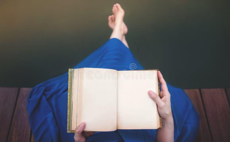 Junge Frau, die durch Flussufer sich entspannt Sitzen auf Plattform und Ablesen des leeren Buches in der mysteriösen Atmosphäre lizenzfreies stockbild
