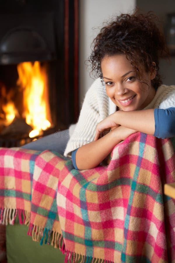 Junge Frau, die durch geöffnetes Feuer sitzt stockfoto