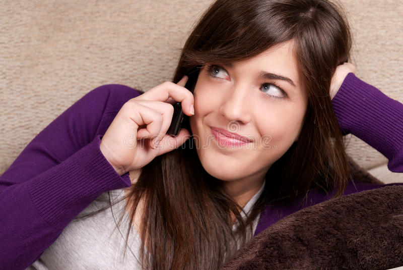 Junge Frau, die durch lächelnde Nahaufnahme des Telefons spricht stockbilder