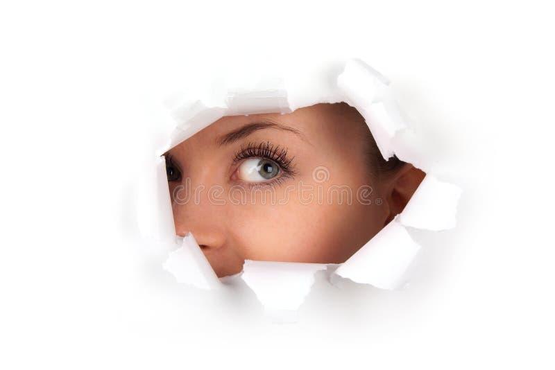 Junge Frau, die durch Loch schaut lizenzfreie stockbilder