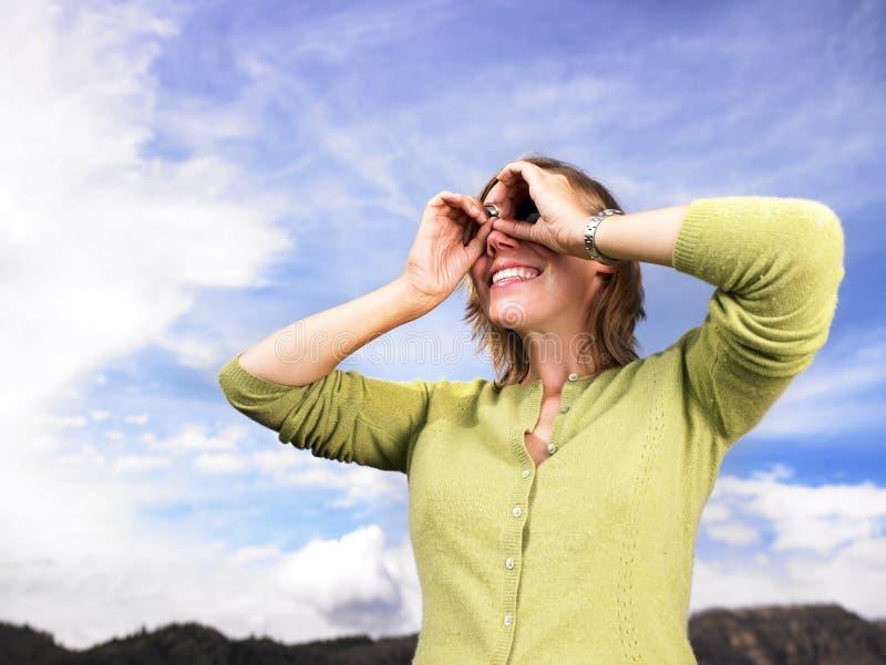 Junge Frau, die durch schalenförmige Hände schaut stockfoto