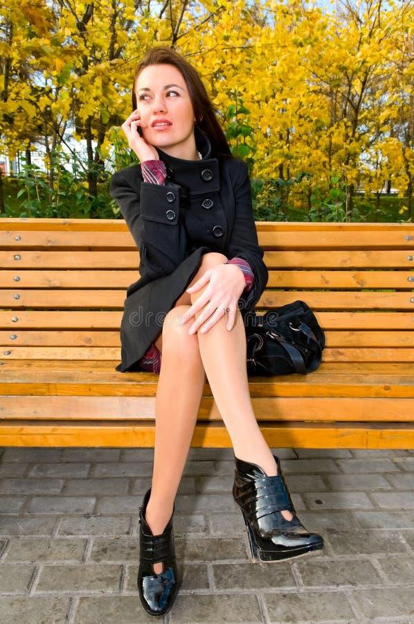 Junge Frau, die durch Telefon spricht lizenzfreie stockfotografie
